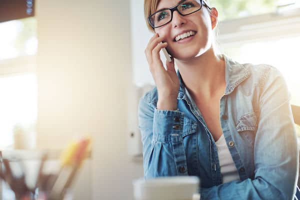bride on cell phone - bride talking to wedding planner on cell phone - updating clients regarding postponing wedding- working from home during COVID 19 - postponing your wedding during COVID 19