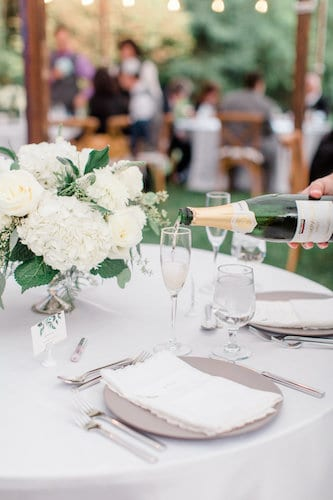 New Jersey Wedding - New Jersey home wedding - New Jersey tented wedding - white centerpieces - modern china - lace napkin - custom menu card- server pouring champagne