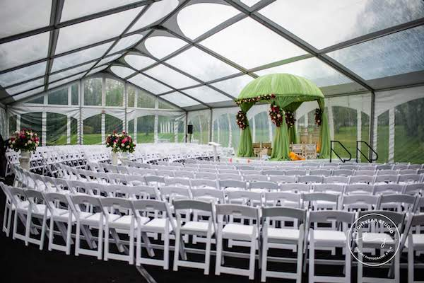 clear tent - wedding ceremony in a clear tent - white garden chairs - Indian wedding ceremony - mandap - green fabric mandap
