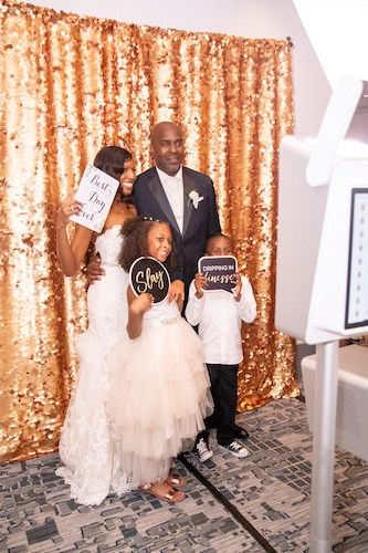 Photo booth - bride and groom taking photos with their children in a Photo Booth - photo booth with a gold backdrop - blended families