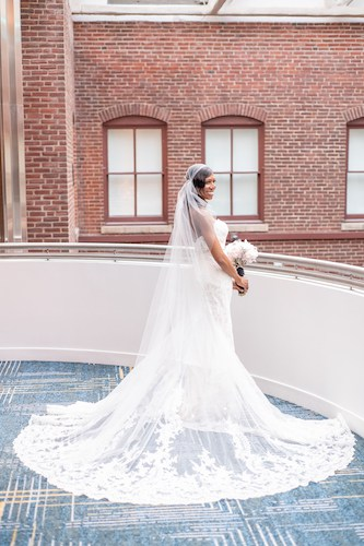 bride in lace wedding gown - bride with long veil - bride on balcony in a lace wedding gown