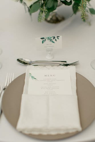 wedding place setting with custom menu and place cards set with a taupe charger plate and fancy napkin fold
