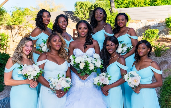 bridal party in teal dresses posing with bride before ceremony