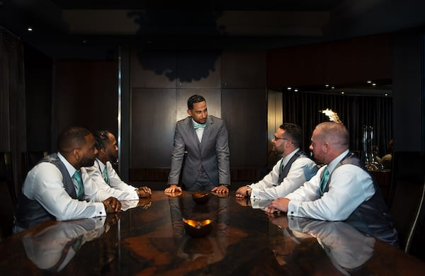 Groom and Groomsmen in charcoal suits with teal ties waiting for wedding ceremony
