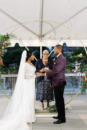 bride and groom exchanging wedding vows in front of a gold moon gate wedding structure