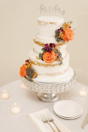 three tiered naked wedding cake with purple and orange flowers sitting on a crystal cake stand