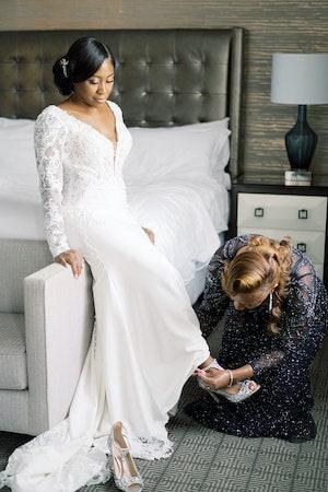 bride's mother helping her get dressed