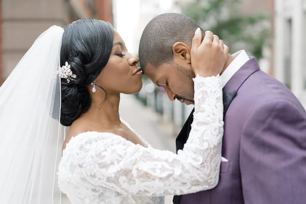 bride kissing groom's forehead on the steps of the Union League of Philadelphia