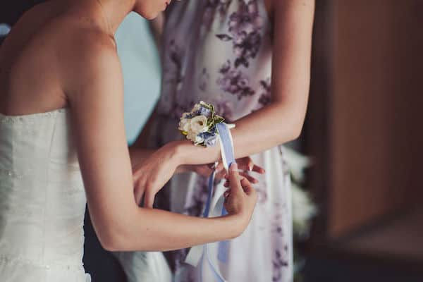 bride placing a wrist corsage on a special guest