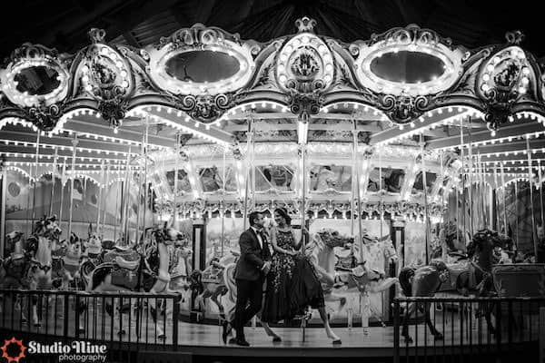 South Asian bride and groom riding the carousel at Philadelphia's Please Touch Museum
