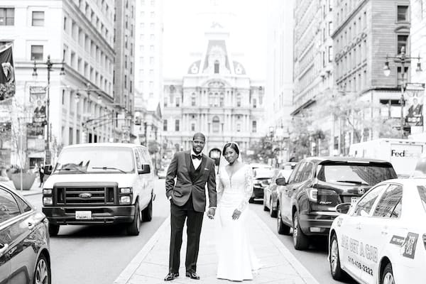 Black bride and groom posing for wedding photos on South Broad Street in front of Philadelphia's City Hall
