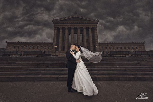 Hispanic bride and groom posing for photos on the step of the Philadelphia Museum of Art