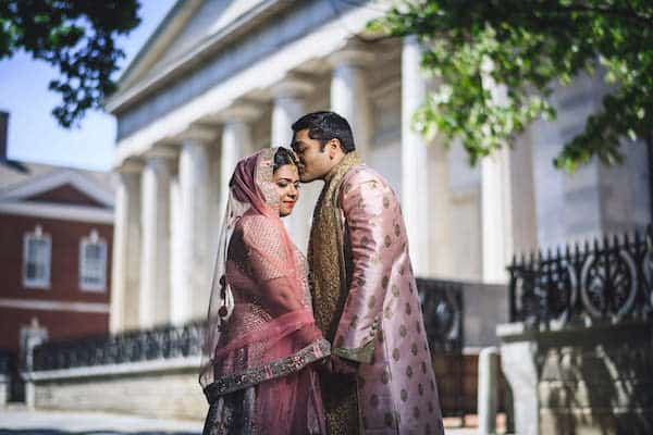 South Asian bride and groom posing for wedding portraits on the steps of the iconic Second Bandk of the United States in Old City Philadelphia