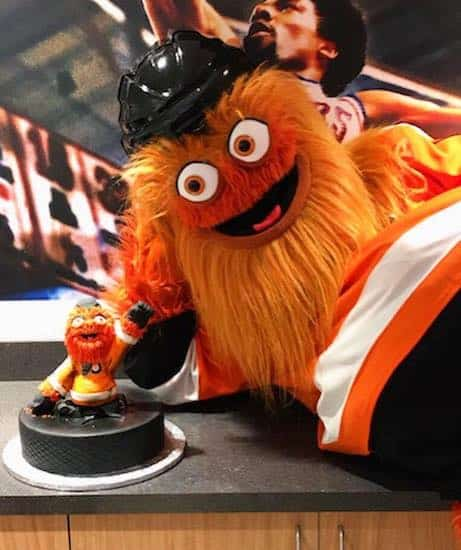 Iconic Philadelphia Flyers mascot Gritty posing in front of a Gritty themed cake by Bredenbeck's Bakery