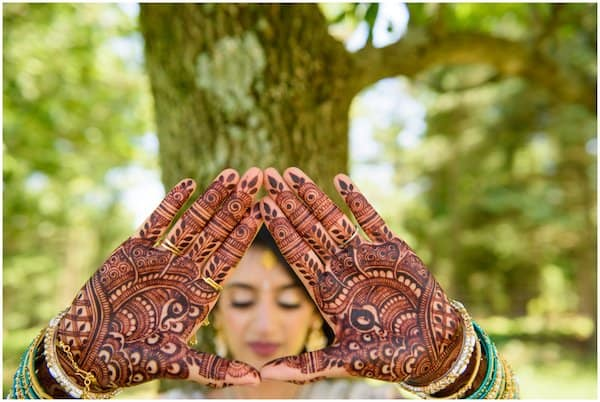 beautiful Indian bride showing henna on the palms of her hands