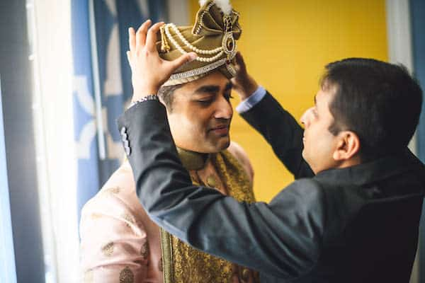 man helping South Asian groom dress for his Philadelphia wedding
