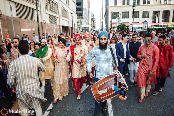 a traditional drummer and wedding guests leading a South Asian groom though the streets of Philadelphia