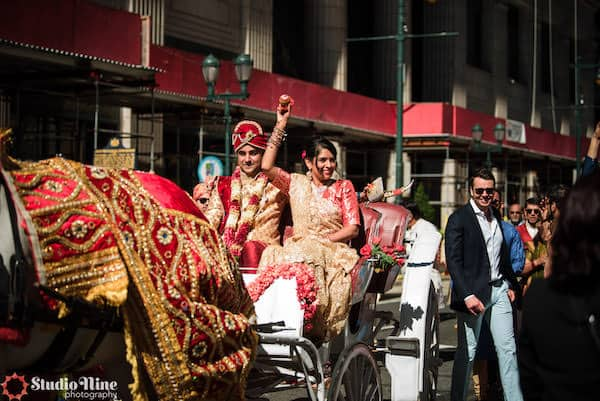 South Asian bride and groom riding in a decorated horse and carriage after their Philadelphia wedding