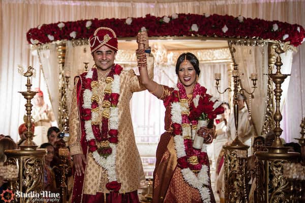 Philadelphia South Asian bride and groom standing under a gold and red mandap