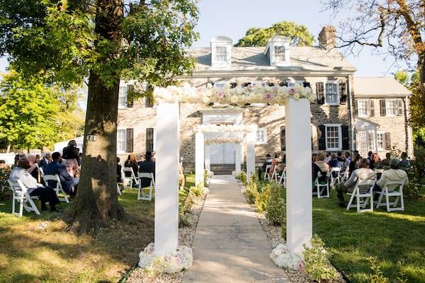 a line of elegant white wedding arches lining the aisle of a Philadelphia-home wedding