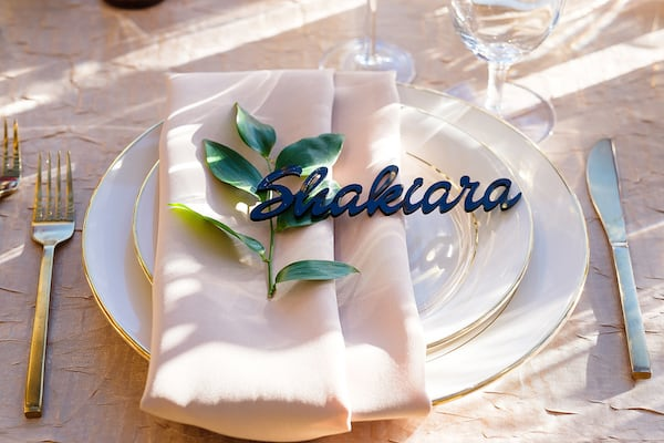 elegant gold layered place setting with custom acrylic name at a micro wedding
