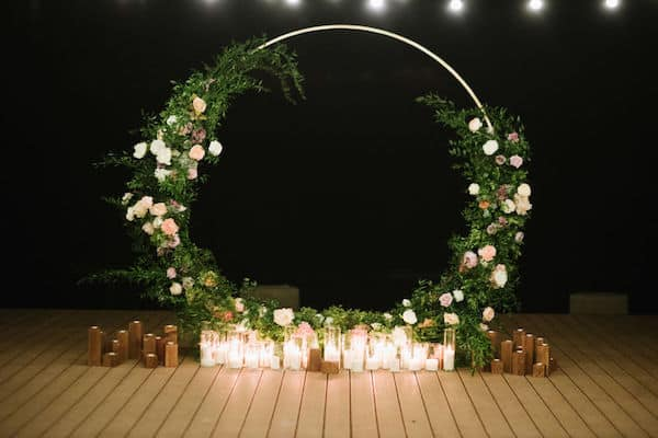 wedding ceremony structure draped in lush greenery that really makes the flowers pop