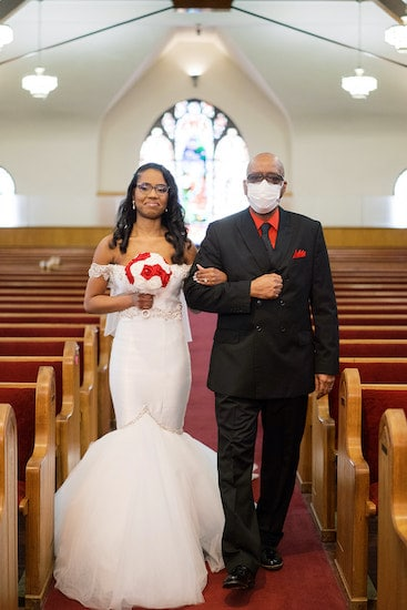 bride walking down the aisle escorted by family member wearing a mask