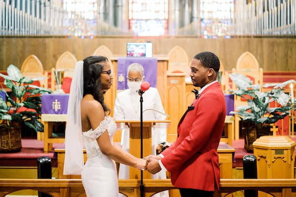 bride and groom exchanging wedding vows in a socially distant wedding ceremony officiated by a masked officiant at St Matthew AME in Philadelphia