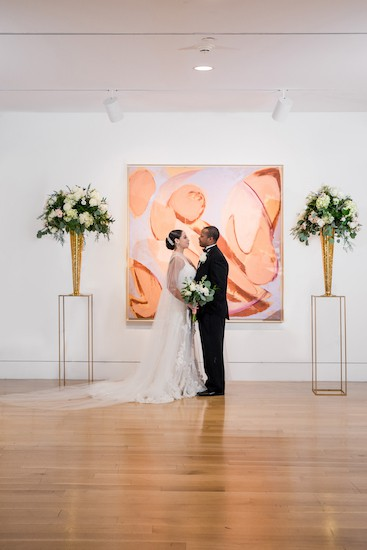 Black bride and groom standing between modern hunter green and gold arrangements at PAFA