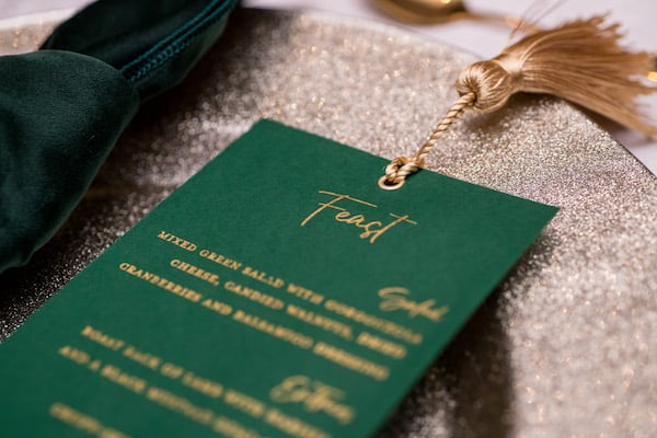 Hunter green and gold place setting with a custom menu card and velvet napkin on a gold charger plate