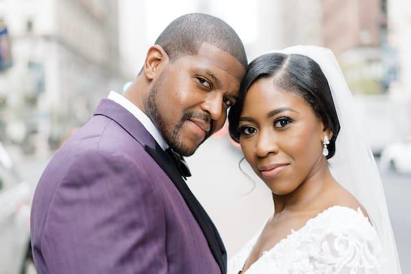 Philadelphia bride and groom posing for wedding photos on South Broad Street near Philadelphia City Hall