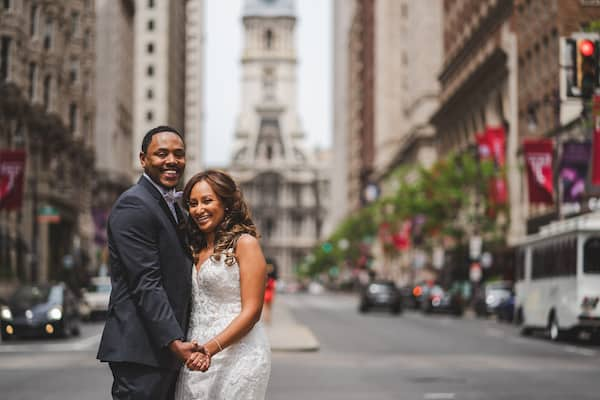 Brid mand groom in the middle of South Broad Street with Philadelphia City Hall in the background