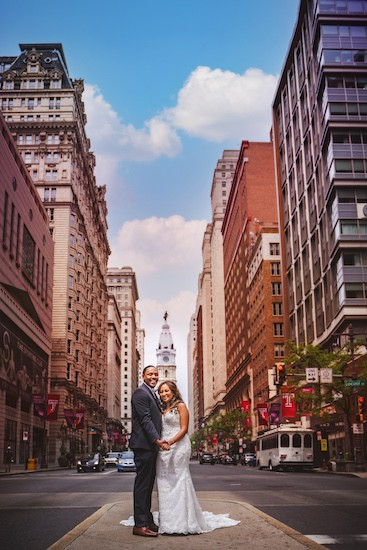 bride and groom on South Broad Stree with Philadelphia City Hall in the background
