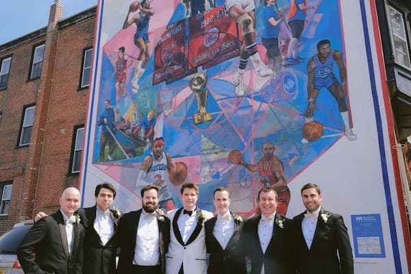 groom and wedding party posing for wedding photos in front of a Philadelphia sports mural
