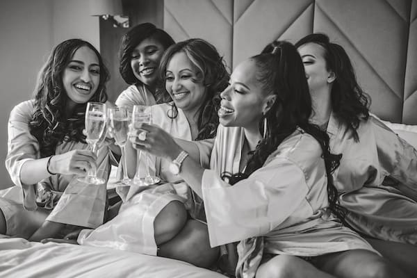 bride and her bridal party wearing robes and toasting with champagne
