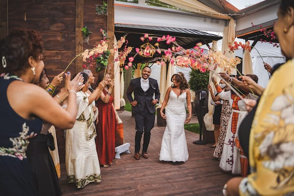 Philadelphia bride and groom entering under an arch of flowers to entered to an Eritrean song, 'Lega Shibo' by Hani Mihreteab