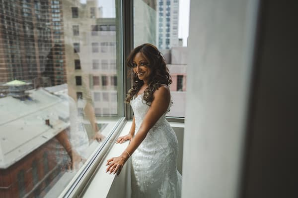bride in a lace wedding gown looking out the window at traffic on South Broad Street