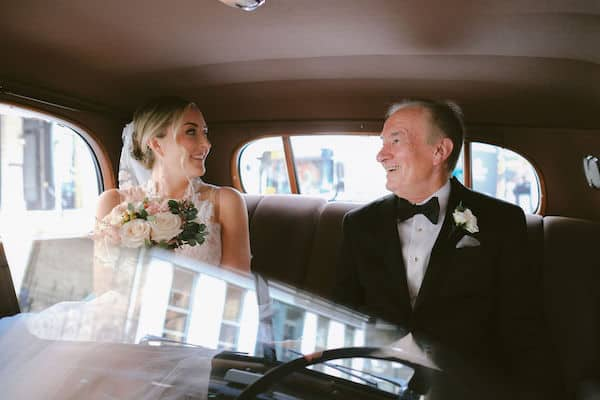 bride and her father in a vintage car on the way to her wedding ceremony