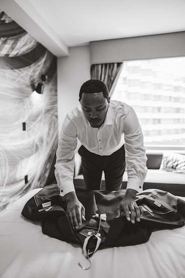 groom fixing his jacket in preparation for his first look with his bride