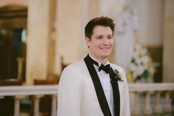 smiling groom as his wedding party enters the church