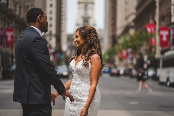 smiling bride and groom standing in the middle of South Broad Street during their first look