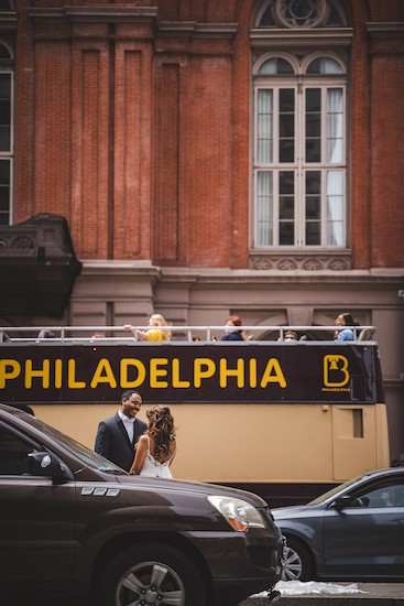 Philadelphia double decker tour bus stops as bride and groom have their first look in front of the Academy of Music